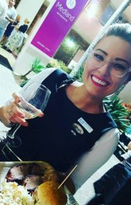 woman wearing glasses holding a glass of wine at dinner