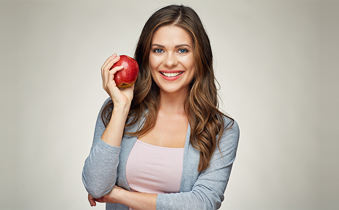woman holds apple she is about to eat with Invisalign