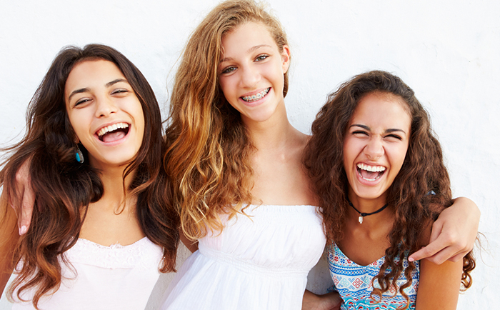 three young girls wonder how braces know where to move the teeth of their friend